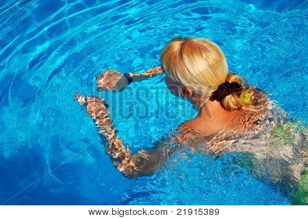 Young Adult Girl Swimming In The Pool