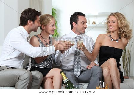 Two couples celebrating with champagne