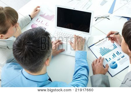 Three business people sitting at table with papers and laptop and planning