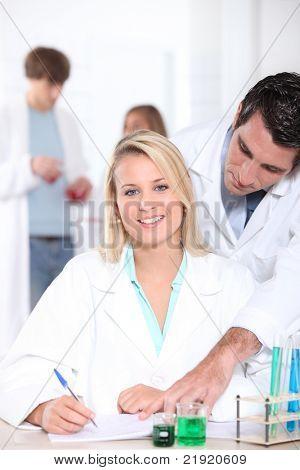 Estudiante de química, ayudado por su profesor