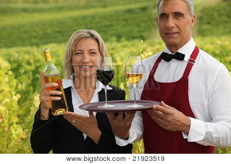 Couple serving wine in a vineyard