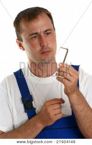 Craftsmen In Blue Overalls Holding An Allen Key