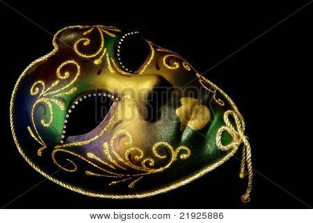 Golden Venetian mask, isolated on black background.