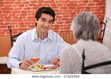 young man having lunch with his grandmother