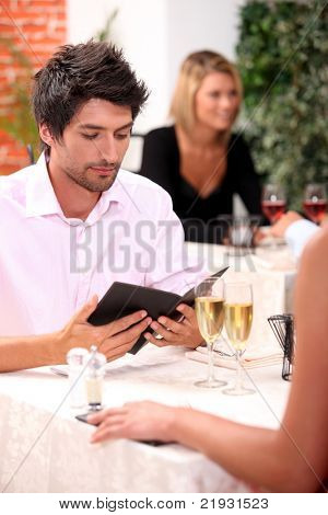 Young man looking at a menu in a restaurant
