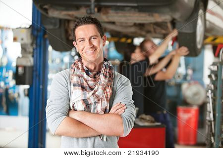 Portrait of a male happy customer in an auto repair shop with mechanics in background