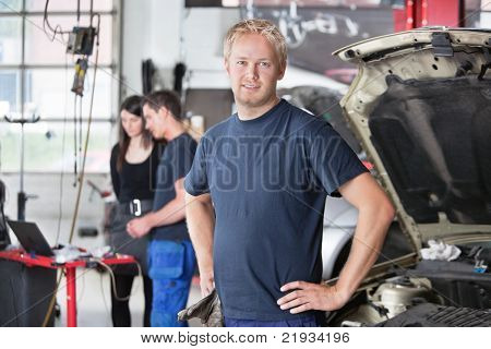Portrait of a  young mechanic in auto repair shop with customer in background