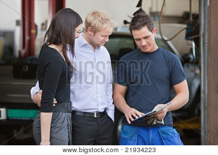 Mature couple standing with mechanic outside the garage