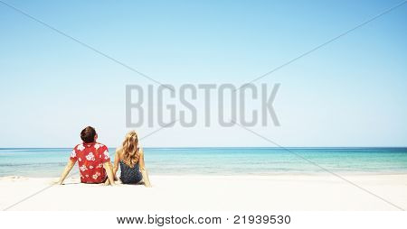 Young couple sitting on white sand by sea and looking to a blue clear sky
