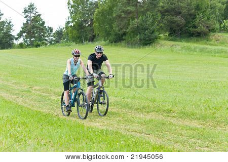 Sport Happy Couple Riding Bicycles In Coutrynside