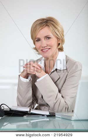 Mujer sentada en su escritorio con ordenador portátil y diario abierto