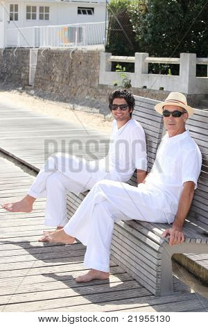 Men sitting on a bench on a sunny day