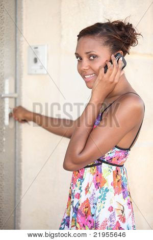 black woman wearing a summer dress coming home and calling