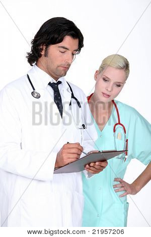 Doctor going over a patient's record with his assistant