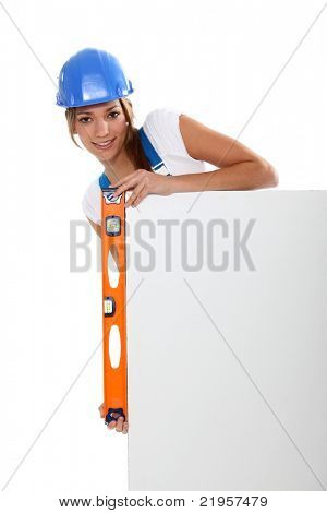 Woman checking a blank board is straight with a spirit level