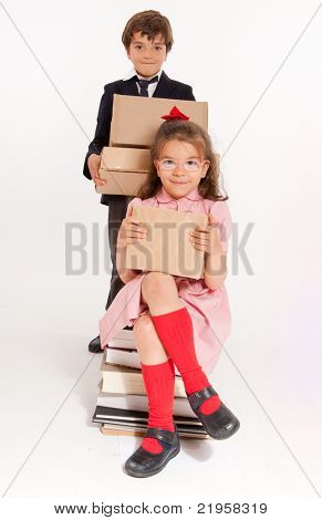 Um menino e uma menina em roupas de escola com uma pilha de livros e caixas