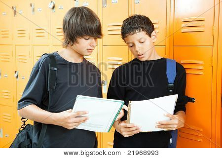 Teenage boys by lockers, comparing answers in their homework workbooks.