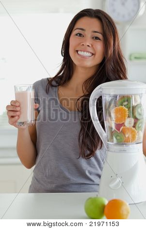 Lovely Woman Using A Blender While Holding A Drink