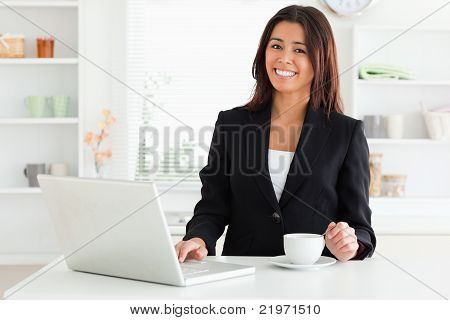 Attractive Woman In Suit Enjoying A Cup Of Coffee While Relaxing With Her Laptop