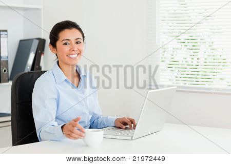 Beautiful Woman Relaxing With Her Laptop While Enjoying A Cup Of Coffee