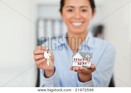 Attractive Woman Holding Keys And A Miniature House While Looking At The Camera