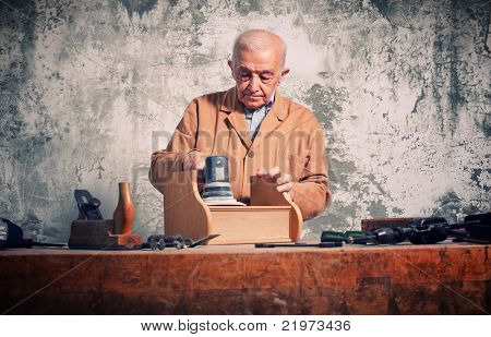 man at work with electric grinder on wood furniture part