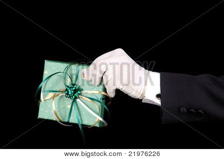 Formal Gloved Hand and Wrapped Christmas Present over black background