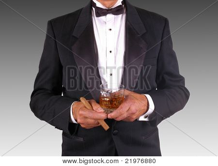 Man in tuxedo holding cocktail and cigar over gradated gray background -torso only