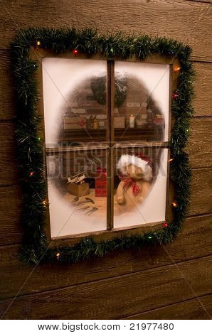 Looking Through Window into Santa Claus' Workshop with toys on workbench in front of brick fireplace. Vertical Composition.