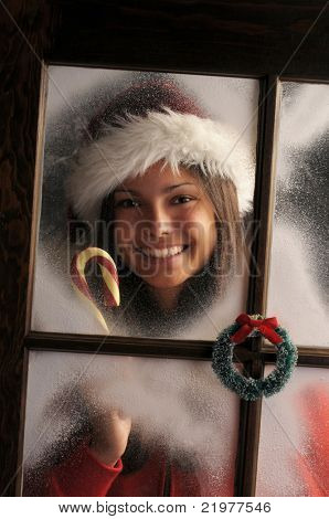 Smiling Teenage girl in window with frost holding candy cane vertical composition at a slant