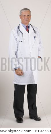 Middle Aged Doctor wearing a Lab Coat one hand in pocket full length over gray background vertical format