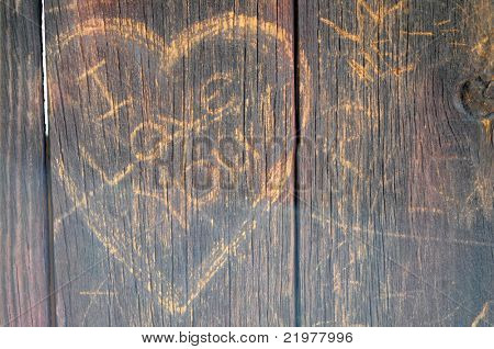 The Words I Love You inside a heart scratched into the weathered wood siding of an old barn.