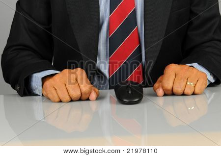 Closeup of a businessman seated at his desk with computer mouse and both ands clenched on desk top. Horizontal format showing only hands and torso and desk.