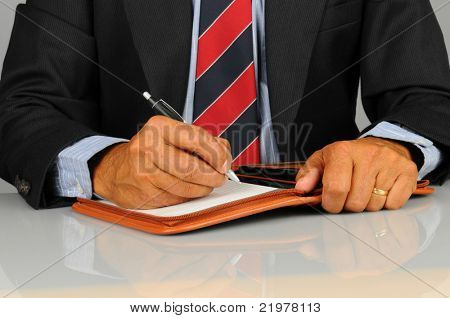 Closeup of a businessman seated at his desk and writing in notebook. Horizontal format showing only hands and torso and desk top.