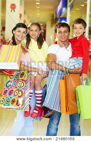 Retrato de casal com dois filhos e sacos de compras olhando para câmera e sorrir