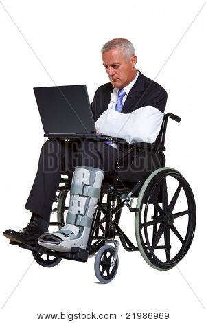 Photo of an injured businessman sitting in a wheelchair working on a laptop computer, isolated against a white background.