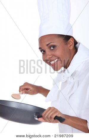 Female chef in uniform with a deep frying pan and wooden spoon