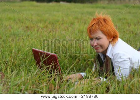 Young Woman With Red Notebook On Grass