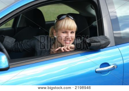 Young Blond Woman In A Blue Car. She Is Smiling Happy