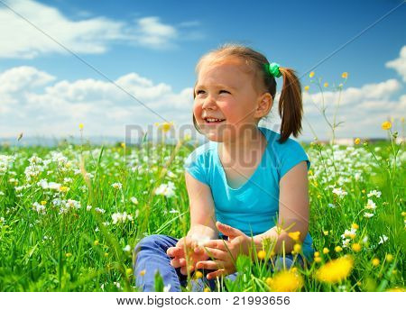 Little Girl Is Playing On Green Meadow