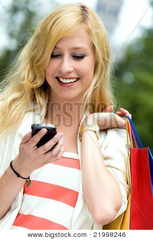 Woman with shopping bags using mobile phone