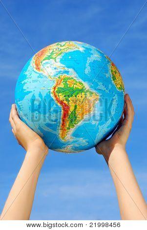 Globe In Hands Against Blue Sky