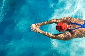 foto of athletic woman  - Athletic swimmer is diving in a swimming pool - JPG