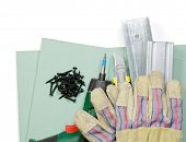 Plasterboard tools set with metal studs, screws, screwgun, cutter and protective gloves on white bac