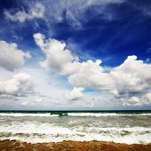 Sea with waves and blue sky with fluffy clouds poster