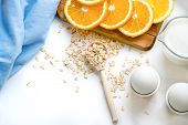 Oat Flakes Plate With Milk, Orange, Eggs On A Wooden White Table. Top View Of Healthy Oat Flakes Bre poster
