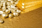 picture of gold nugget  - fine gold ingots and nuggets on a wet golden background