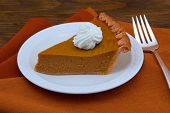 stock photo of pumpkin pie  - A Slice of Pumpkin Pie on Wood Table - JPG