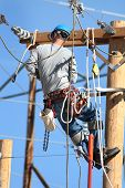 foto of lineman  - an electrical lineman working on lines outside - JPG