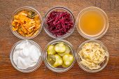 a set of fermented food great for gut health - top view of glass bowls against rustic wood:  kimchi, poster